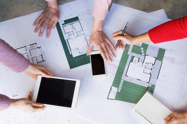 Closeup de arquitetos trabalhando com desenhos e usando gadgets Foto gratuita