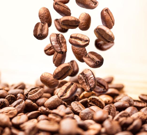 Closeup de cair ou voar grãos de café em branco Foto Premium