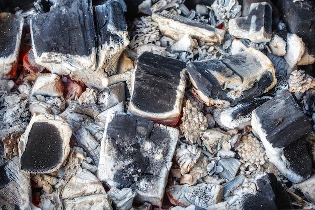 Closeup de carvões de madeira em decomposição e cinzas no braseiro Foto Premium