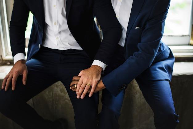 Closeup de casal gay segurando as mãos sentados juntos Foto Premium