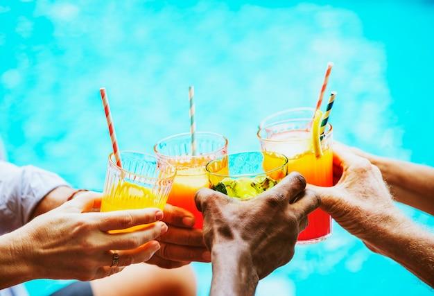 Closeup de diversas mãos tinindo bebidas juntos Foto Premium