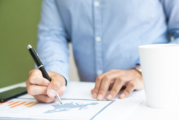 Closeup de especialista em marketing masculino, analisando o gráfico de barras Foto gratuita