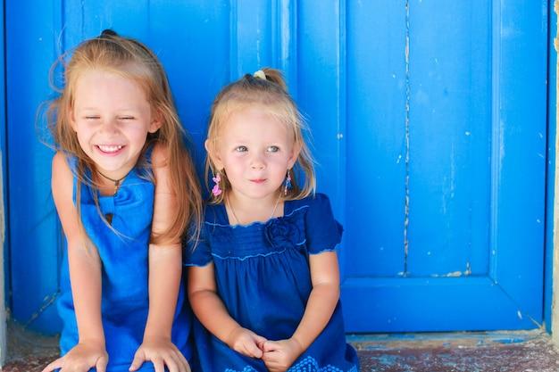 Closeup de garotinhas adoráveis sentado perto da antiga porta azul na aldeia grega, emporio, santorini Foto Premium