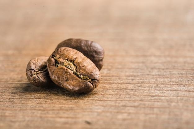 Closeup de grãos de café sobre fundo de madeira com copyspace Foto Premium