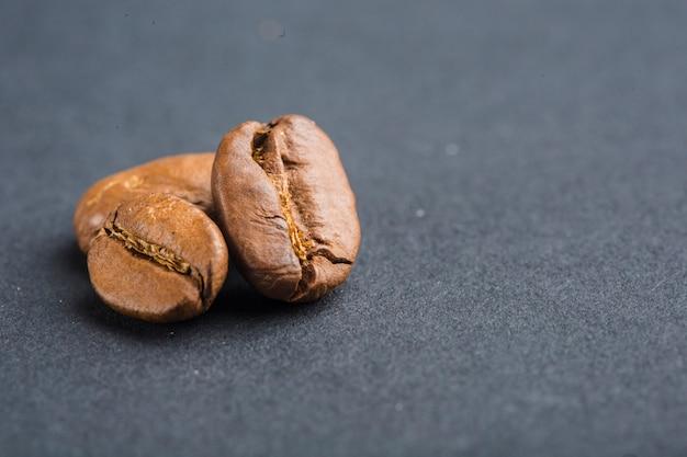Closeup de grãos de café sobre fundo preto com copyspace Foto Premium