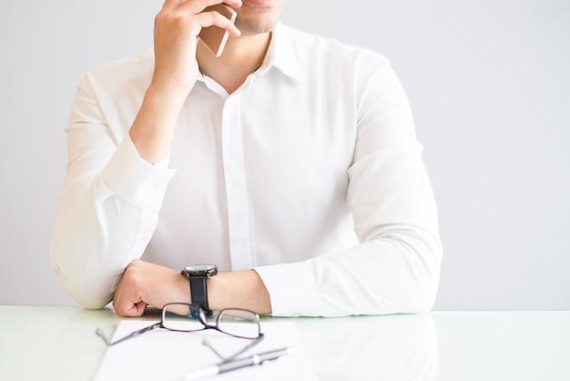 Closeup, de, homem, chamando, smartphone, em, escritório Foto gratuita