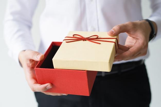Closeup de homem de negócios, abrindo a caixa de presente Foto gratuita