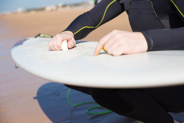 Closeup, de, homem jovem, encerando, surfboard, ligado, ensolarado, praia Foto gratuita