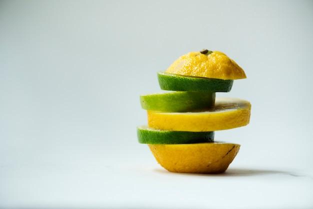 Closeup de laranjas misturado com pedaços de limão isolado no branco Foto gratuita