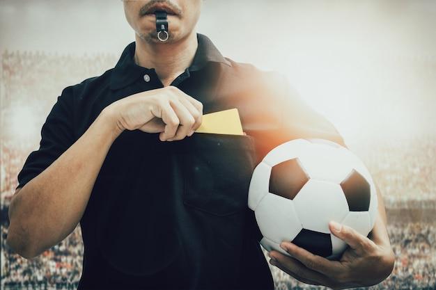 Closeup de mão de árbitro de futebol segurando cartão amarelo isolado no branco com traçado de recorte Foto Premium