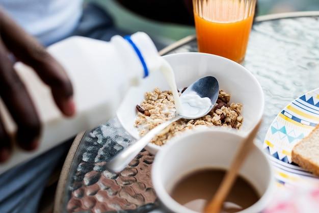 Closeup, de, mão, leite derramando, em, cereal Foto Premium