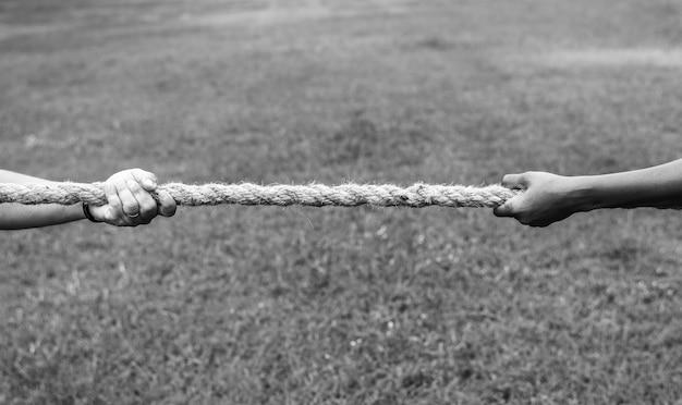 Closeup de mão puxando a corda no jogo de cabo de guerra Foto gratuita