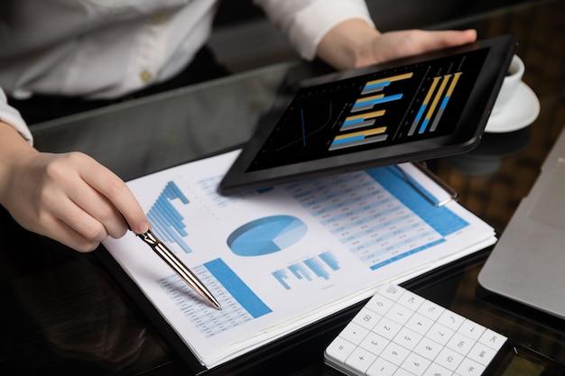 Closeup de mão segurando o tablet e caneta no gráfico Foto Premium
