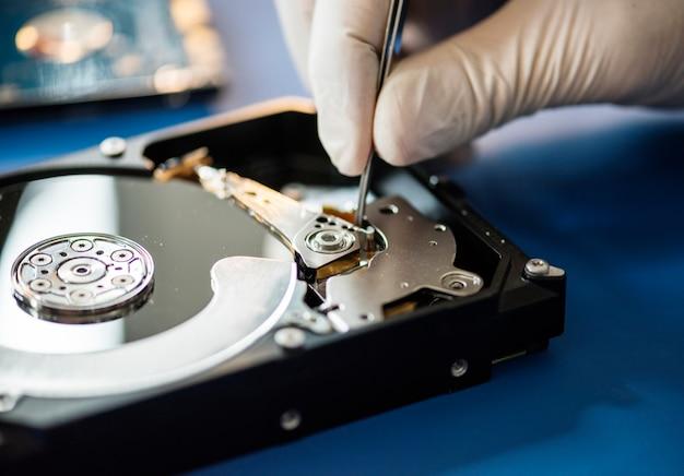 Closeup, de, mãos, com, pinça, e, computador, disco rígido Foto Premium