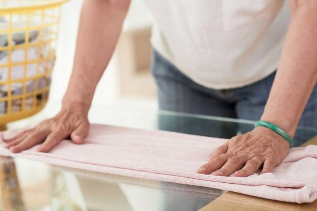 Closeup de mãos de mulher irreconhecível dobrar roupas secas Foto gratuita