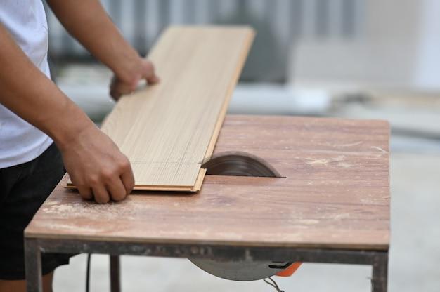 Closeup de mãos de um carpinteiro trabalhando com equipamentos na bancada de madeira. Foto Premium