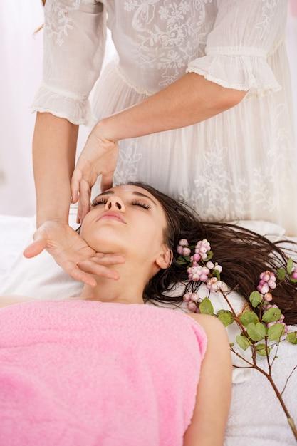 Closeup de mãos massagista feminino fazendo massagem facial com cuidado Foto gratuita