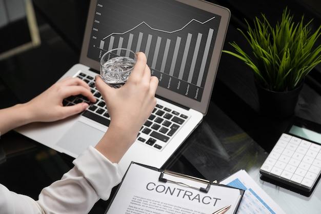 Closeup de mãos segurando um copo de água e se familiarizando com o contrato Foto Premium