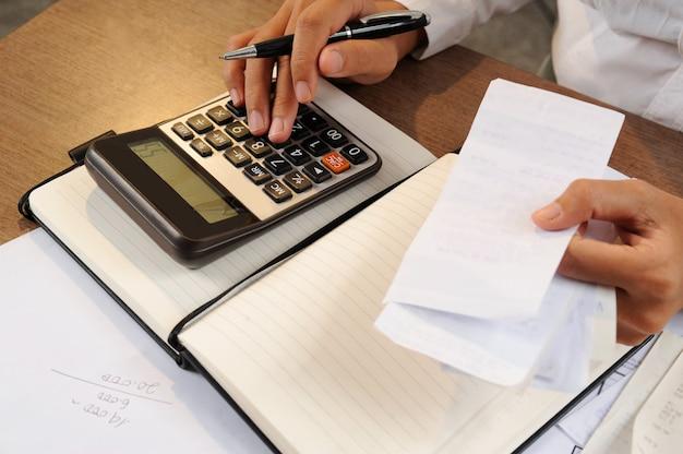 Closeup, de, mulher, calculando contas, ligado, calculadora Foto gratuita