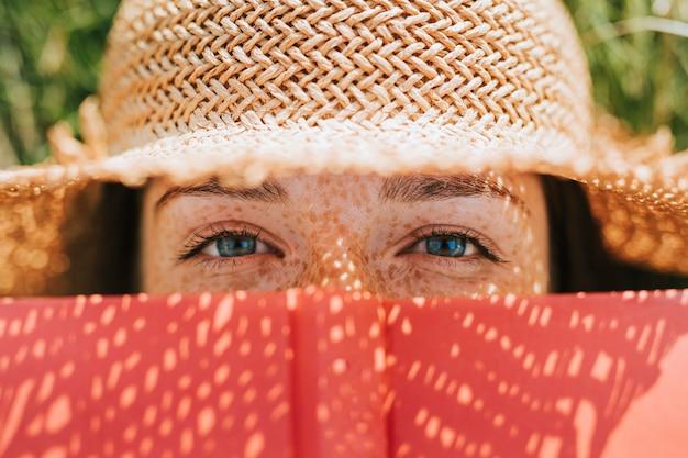 Closeup, de, mulher, cobertura, dela, rosto, com, um, livro vermelho Foto gratuita