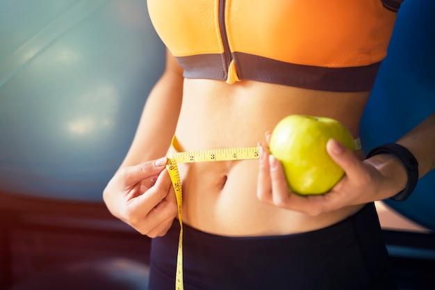 Closeup de mulher jovem esporte usando fita métrica no abdômen com maçã verde na mão Foto Premium