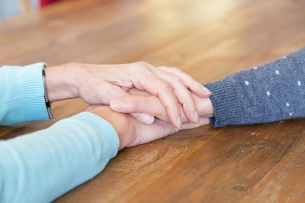 Closeup, de, mulher sênior, segurando, filhas, mão Foto gratuita