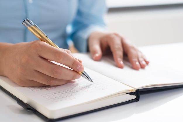 Closeup, de, mulher, usando, diário, e, agendamento Foto gratuita