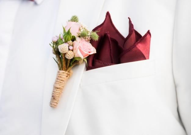 Closeup de noivo boutonnière na lapela de terno Foto gratuita