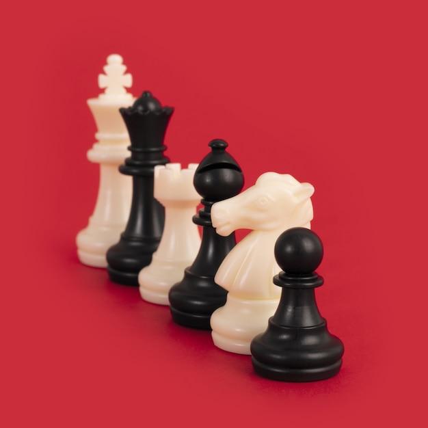 Closeup de peças de xadrez preto e branco alinhadas em um vermelho brilhante Foto gratuita