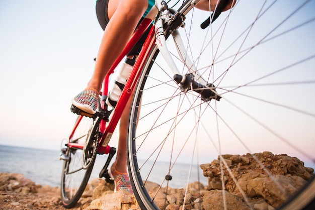 Closeup de pernas de mulher ciclista andando de bicicleta na trilha ao ar livre Foto Premium