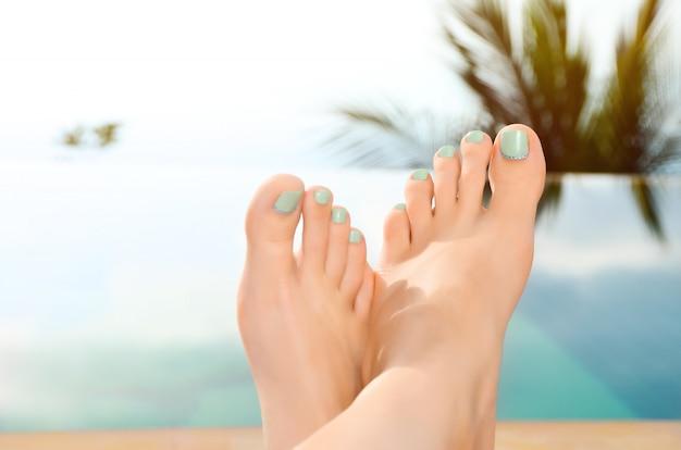 Closeup de pés femininos. garota relaxante à beira da piscina. Foto gratuita