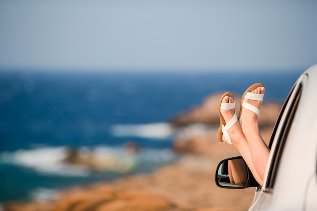 Closeup de pés femininos mostrando do mar de fundo de janela de carro Foto Premium