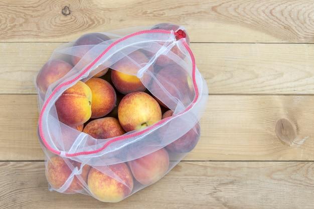 Closeup de pêssegos em uma sacola de compras na madeira Foto Premium