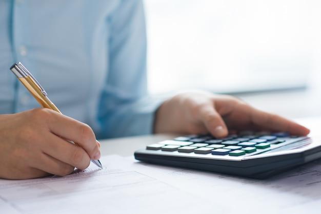Closeup, de, pessoa, assinando, documento, e, usando, calculadora Foto gratuita