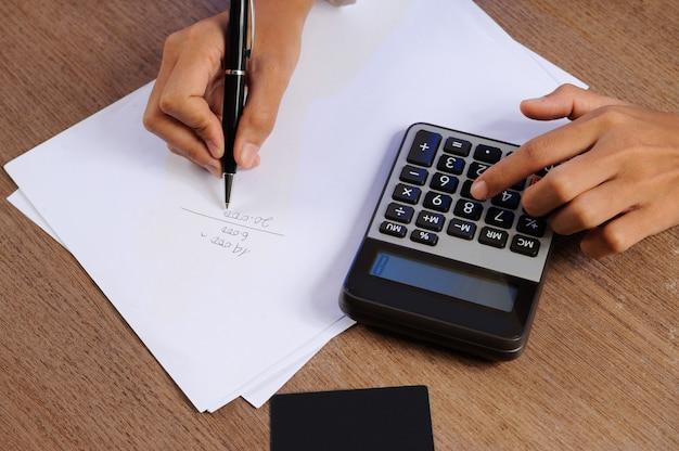 Closeup, de, pessoa, calculando, ligado, calculadora, e, escrita Foto gratuita