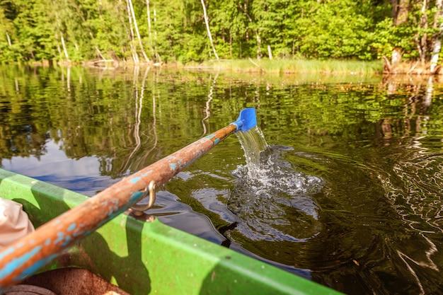 Closeup de remo de barco a remo movendo-se na água em um lago verde com ondulações Foto Premium