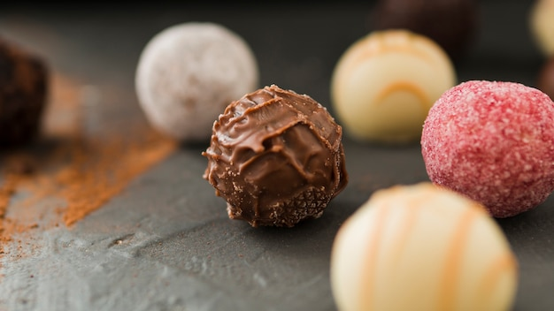 Closeup, de, vário, redondo, chocolates, ligado, tabela preta Foto gratuita