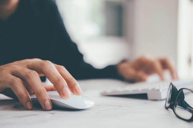 Closeup empresário usando mouse e teclado de computador Foto Premium