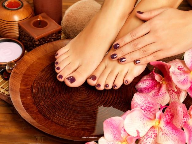 Closeup fotografia de um pé feminino no salão spa no procedimento de pedicura. pernas femininas na água decoram as flores. Foto gratuita