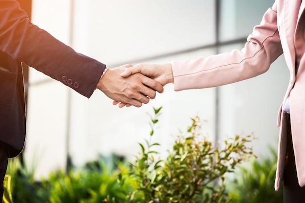 Closeup handshake de reunião amigável entre mulher de negócios e empresário com luz solar. Foto gratuita