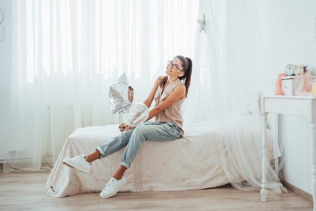 Closeup linda garota morena no, sorrindo amplamente e brincando com balões transparentes e prata. Foto Premium