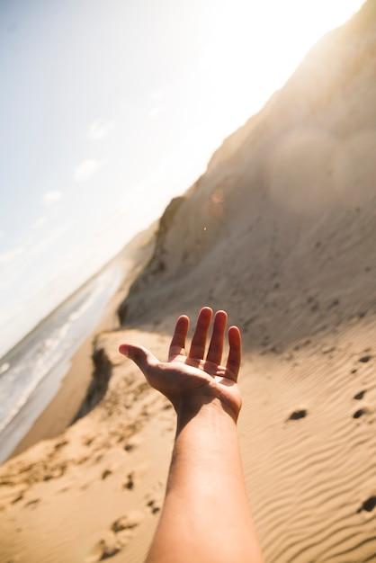 Closeup mão apontando na praia paisagem Foto gratuita