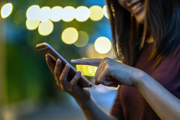 Closeup mão da mulher asiática usando smartphone e tela tocante no parque ao ar livre Foto Premium