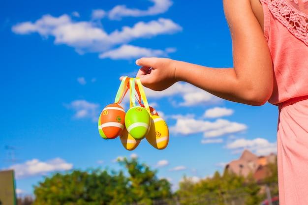 Closeup mão de uma menina segurando ovos de páscoa coloridos fundo do céu azul Foto Premium