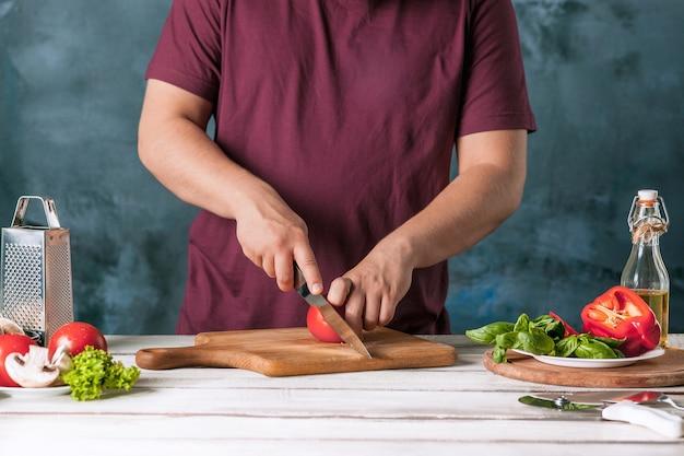 Closeup mão do chef padeiro fazendo pizza na cozinha Foto gratuita