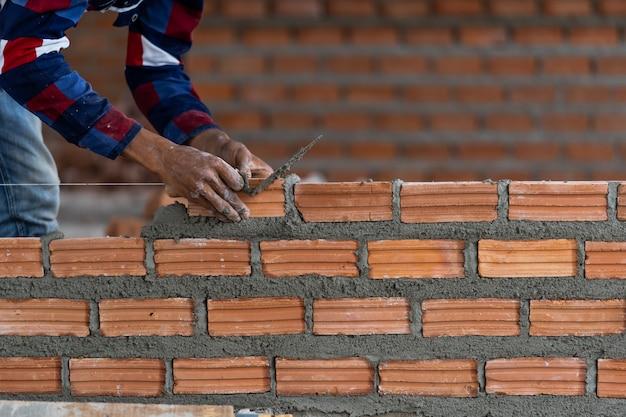 Closeup mão profissional trabalhador da construção civil colocar tijolos no novo site industrial Foto Premium