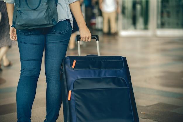 Closeup mão segurando a bagagem sobre a placa de vôo para check-in Foto Premium