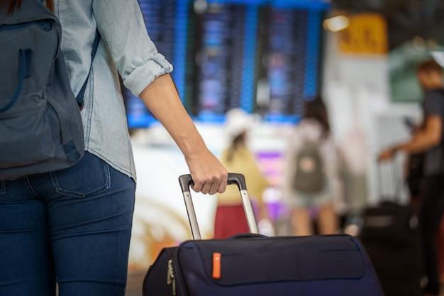 Closeup mão segurando a bagagem sobre a placa de vôo para o check-in na informação do voo Foto Premium