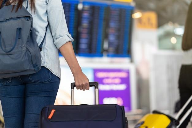 Closeup mão segurando a bagagem sobre a placa de voo para o check-in no voo informat Foto Premium
