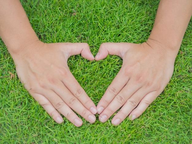 Closeup mãos na grama com a forma de forma de coração Foto Premium